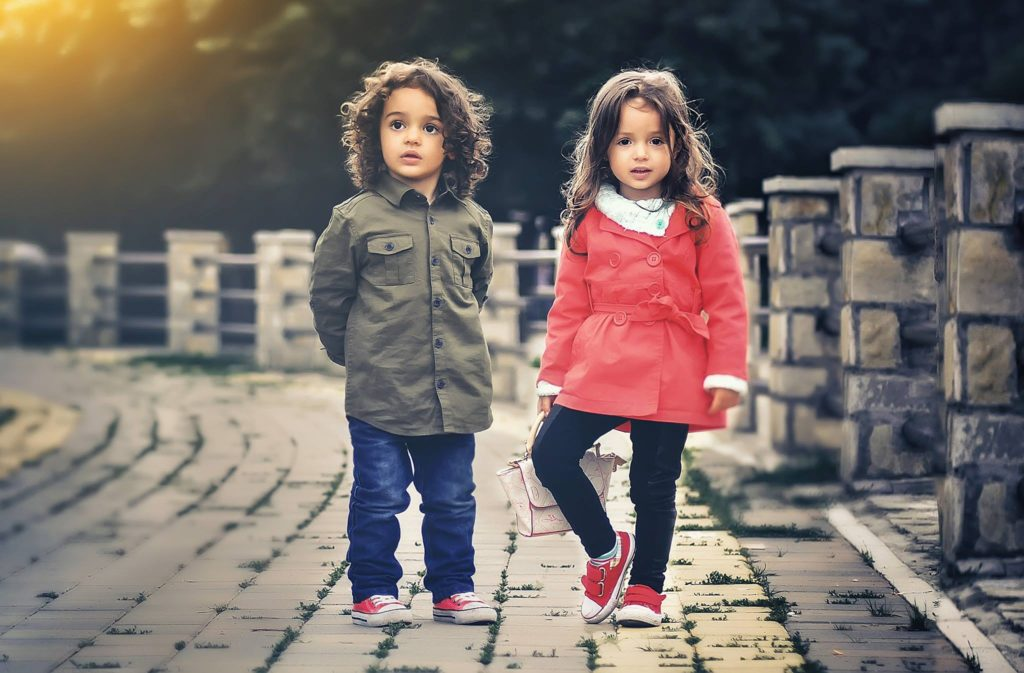 Two beautiful sister who are toddlers dressed in different outfits looking in different directions standing on a bridge